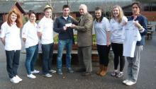 Lion Ron Webb presenting cash and T Shirts to Andy Taylor and his PE Sports group