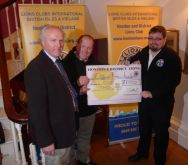 Lion President Steve presenting £1000 cheque to Free Wheelers Dan and Kevin