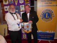 Lions President Brian exchanges bannerettes with visiting Swadlincote President