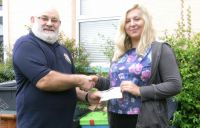 Lion President Brian presenting £97 cheque to Yazmine Hoyle
